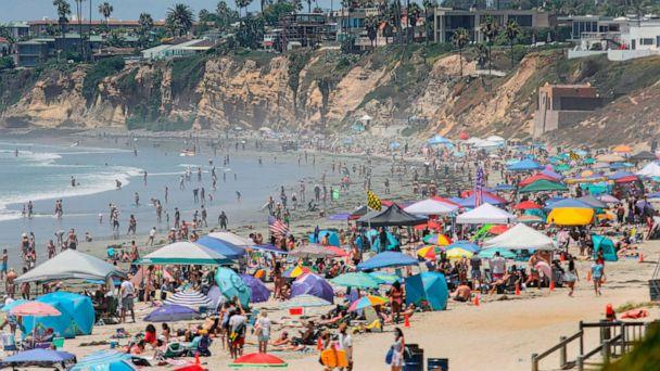 PHOTO: Beachgoers are seen along the shore in the Pacific Beach area of San Diego, California, on July 4, 2020. (Sandy Huffaker/AFP via Getty Images)
