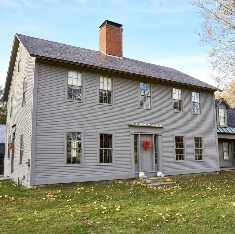 <p>A contrasting red wreath really pops against the gray exterior of this 200-year-old restored New Hampshire farmhouse. A mix of pumpkins on the steps and a row of tiny white pumpkins on the door transom keep the look simple yet seasonal.</p>
