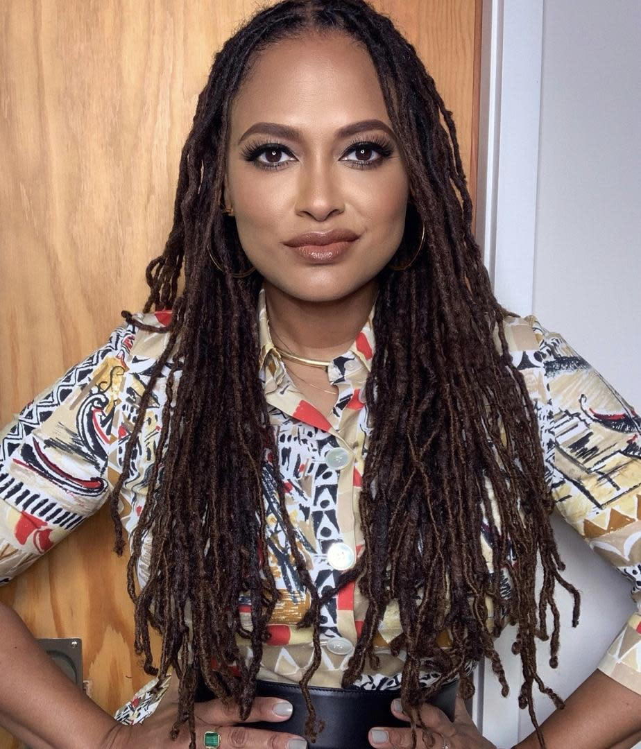 photo of filmmaker Ava DuVernay, a Black woman with long locs standng in front of a door. She is wearing a colorful printed shirt.