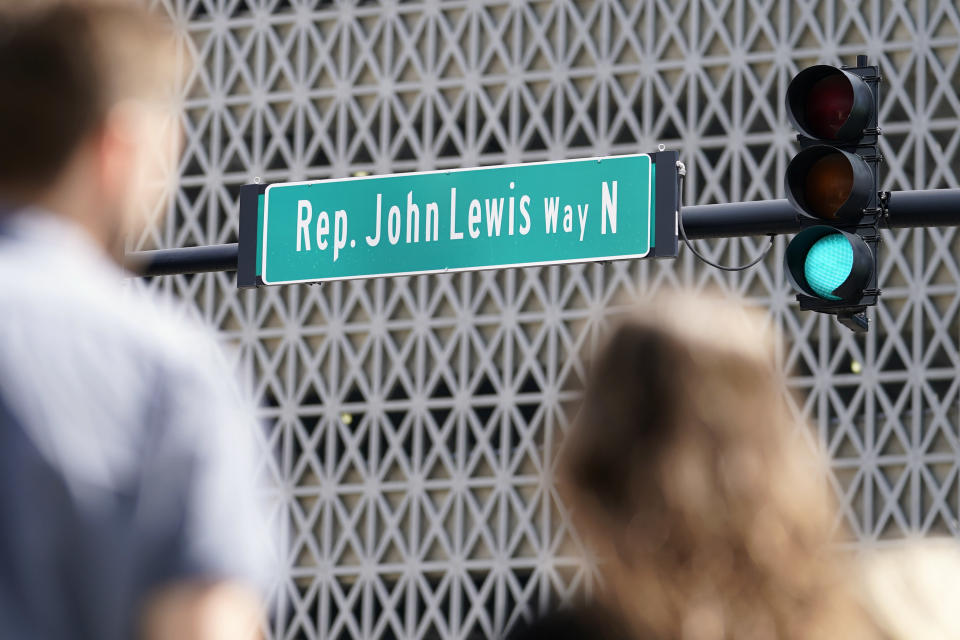 People wait to cross a street that was renamed to honor former Rep. John Lewis Friday, July 16, 2021, in Nashville, Tenn. Nashville leaders on Friday also unveiled a new historical marker remembering Lewis, kicking off a weekend celebrating the civil rights icon. (AP Photo/Mark Humphrey)