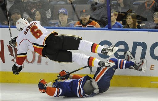 Calgary Flames' Cory Sarich, top, crashes into the Edmonton Oilers' Taylor Hall during the first period of an NHL hockey game in Edmonton, Alberta, on Friday, March 16, 2012. (AP Photo/The Canadian Press, John Ulan)