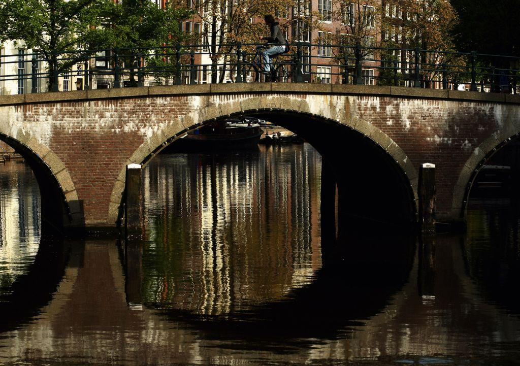 A cyclist makes his way across a canal in Amsterdam, Netherlands.