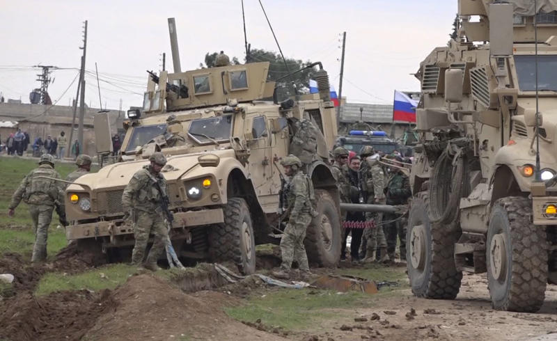 In this frame grab from video, Russian, Syrian and others gather next to an American military convoy stuck in the village of Khirbet Ammu, east of Qamishli city, Syria, Wednesday, Feb. 12, 2020. Syrian media and activists say a Syrian was killed and another wounded in a rare clash between American troops and a group of government supporters in northeast Syria. (AP Photo)