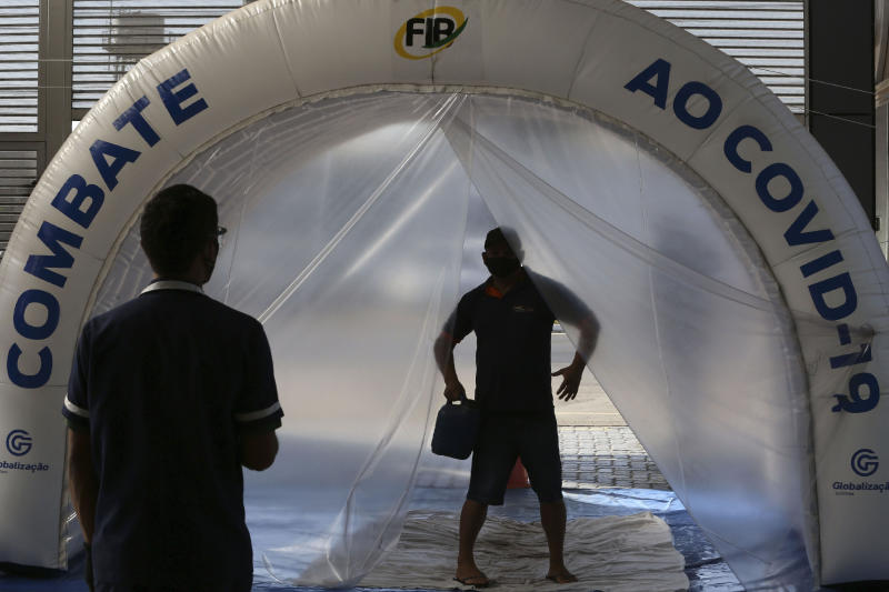 A man passes through a disinfection tunnel amid the COVID-19 pandemic before entering a market of imported products in Brasilia, Brazil, Friday, July 3, 2020. The local government authorized the reopening of markets and street fairs. (AP Photo/Eraldo Peres)