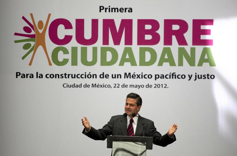 """Enrique Pena Nieto, presidential candidate for the Institutional Revolutionary Party (PRI), speaks during the first Citizens Summit in Mexico City, Tuesday, May 22, 2012. Mexico will hold presidential elections on July 1. The sign behind reads in Spanish """"For the construction of a fair and just Mexico."""" (AP Photo/Eduardo Verdugo)"""