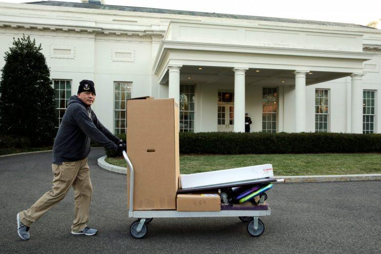 Staff move boxes in and out of the White House.