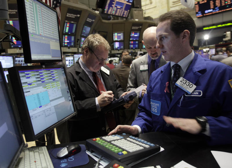 In this Feb. 24, 2011 photo, specialist Glenn Carell, right, works at his post on the floor of the New York Stock Exchange. (AP Photo/Richard Drew)