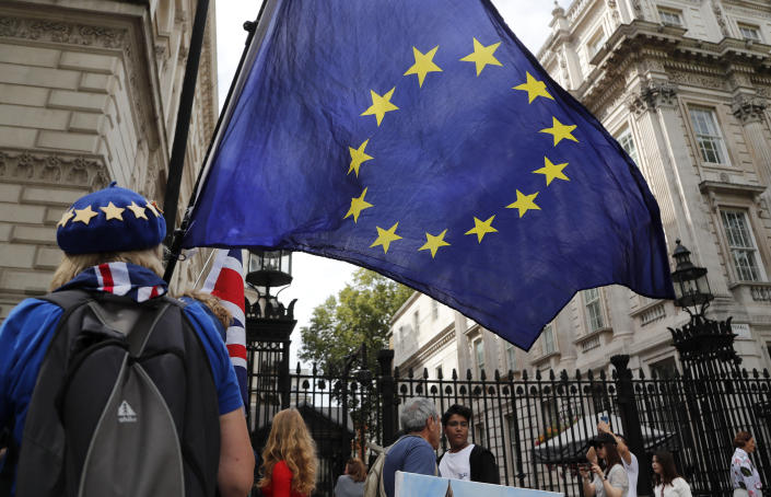 A pro EU protestor waves a European flag outside Downing Street in London, Wednesday, Aug. 28, 2019. Prime Minister Johnson has written to fellow lawmakers explaining his decision to ask Queen Elizabeth II to suspend Parliament as part of the government plans before the Brexit split from Europe. (AP Photo/Frank Augstein)