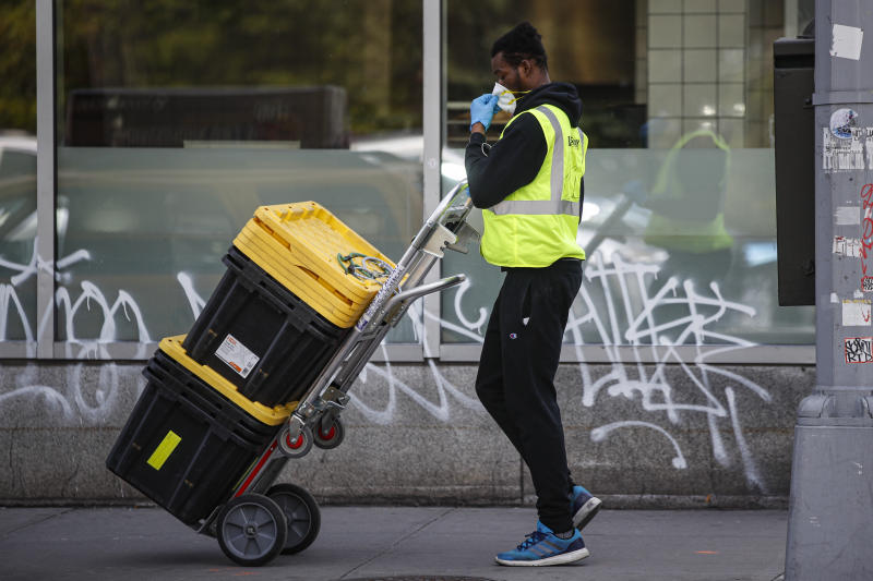 A delivery worker adjusts his mask while wearing personal protective equipment due to COVID-19 and coronavirus concerns before making a pickup outside a Whole Foods Market, Wednesday, April 1, 2020, in New York. (John Minchillo/AP)