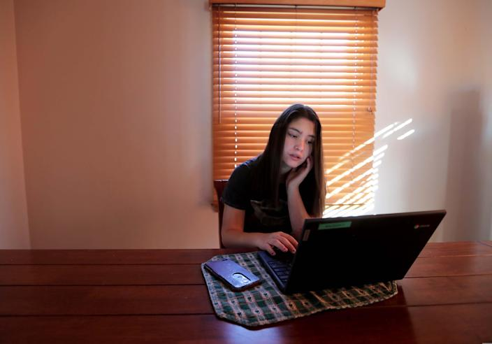 Ruby Rodriguez, a ninth-grade student at St. Anthony High School in Milwaukee, logs on to her English class from her family's dining room. The private school is only teaching students remotely this fall, and Rodriguez struggles to stay motivated.