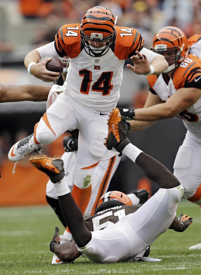 Cincinnati Bengals quarterback Andy Dalton (14) is tripped up by Cleveland Browns linebacker Barkevious Mingo on a short run in the third quarter of an NFL football game Sunday, Sept. 29, 2013, in Cleveland. (AP Photo/Mark Duncan)