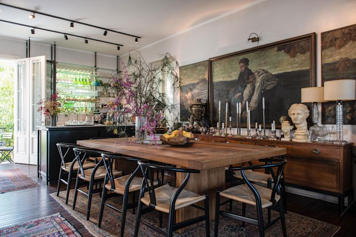 The dining room, with its oak table handcrafted by a local carpenter and Hans Wegner Wishbone Chairs, is the focal point of the house. At the room's center are a series of three late-18th-century oil paintings by the German artist Hugo Walzer.