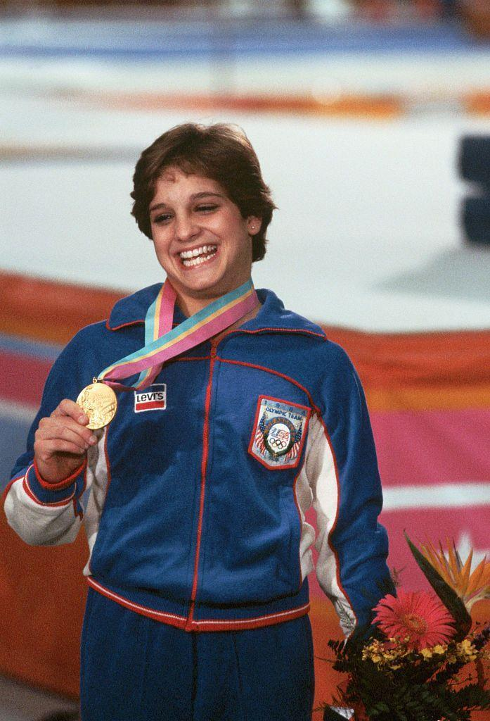 """<p>Mary Lou Retton became a darling of American gymnastics after her performance at the 1984 Los Angeles Olympics. Her routines, two of which earned perfect scores, led her to become the <a href=""""https://www.britannica.com/biography/Mary-Lou-Retton"""" rel=""""nofollow noopener"""" target=""""_blank"""" data-ylk=""""slk:first American woman"""" class=""""link rapid-noclick-resp"""">first American woman</a> to win an individual gold medal in gymnastics. </p>"""