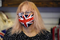 Helen Dawson wears a mask of the British flag while tending to customers at Ye Olde King's Head Shoppe on Thursday, Nov. 19, 2020, in Santa Monica, Calif. The British restaurant and bar in seaside Southern California has been battered the past nine months and was in the process of adapting to new restrictions that took effect Friday, Nov. 20 that would further crimp its recovery even as the prospect of a crippling shutdown loomed. (AP Photo/Marcio Jose Sanchez)