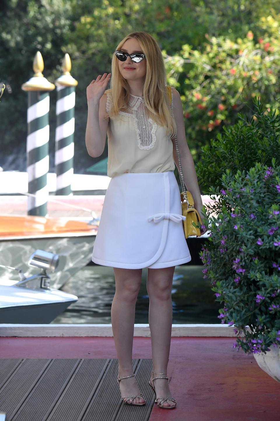 <p>Dakota opted for a Miu Miu mini skirt and lace camisole while arriving at the festival. <em>[Photo: Getty]</em> </p>
