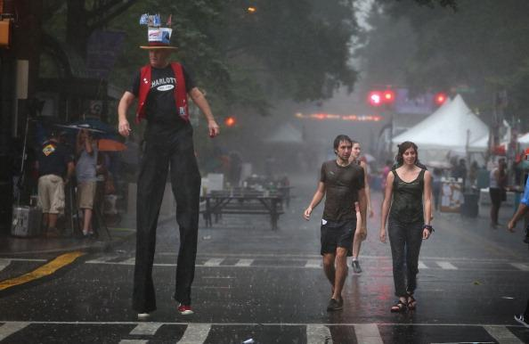 Visitors to CarolinaFest, Charlotte's Labor Day street festival, get caught in a downpour September 3, 2012 in Charlotte, North Carolina. The Democratic National Convention begins tomorrow in Charlotte and runs through Thursday. (Photo by Scott Olson/Getty Images)