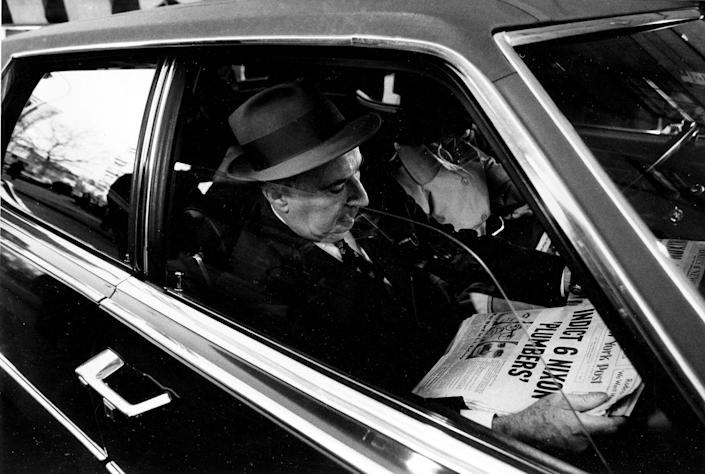 """<p>Former U.S. Attorney General John N. Mitchell reads newspaper front page headline, """"Indict 6 Nixon Plumbers,"""" in his car as he leaves U.S. District Court in New York City on March 7, 1973. Mitchell was on trial for criminal conspiracy in the Watergate scandal. (Photo: Ray Stubblebine/AP) </p>"""