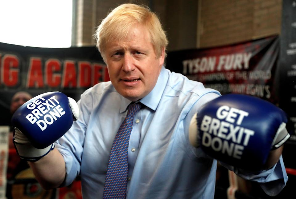 Britain's Prime Minister and leader of the Conservative Party, Boris Johnson wears boxing gloves emblazoned with
