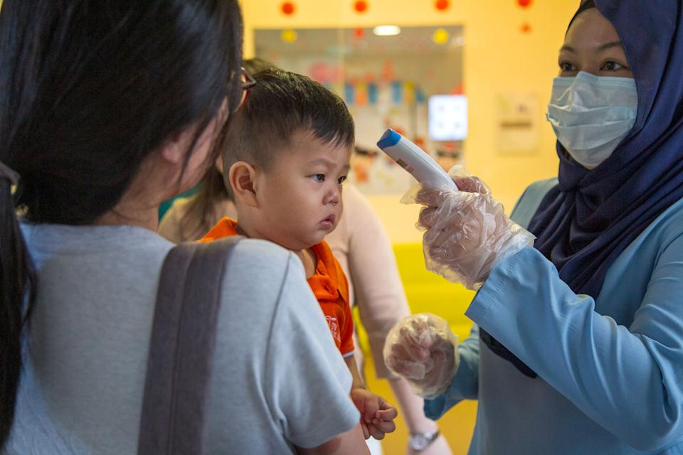 A child being checked for temperature at the My First Skool pre-school branch at Buangkok Crescent. (PHOTO: Dhany Osman/Yahoo News Singapore)