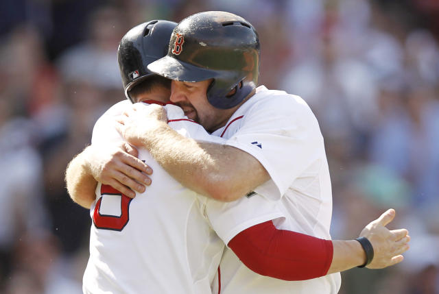 BOSTON, MA - JUNE 24: Kevin Youkilis #20 of the Boston Red Sox is hugged by his replacement at third base Nick Punto #5 after he was removed from the game after tripling against the Atlanta Braves during the eighth inning of Boston's 9-4 win in an interleague game at Fenway Park on June 24, 2012 in Boston, Massachusetts. (Photo by Winslow Townson/Getty Images)