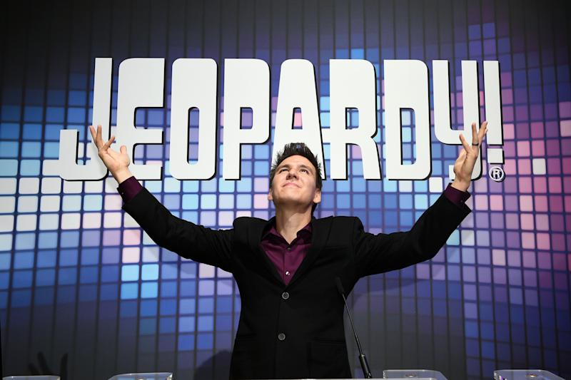 James Holzhauer poses in front of a Jeopardy sign with his arms raised