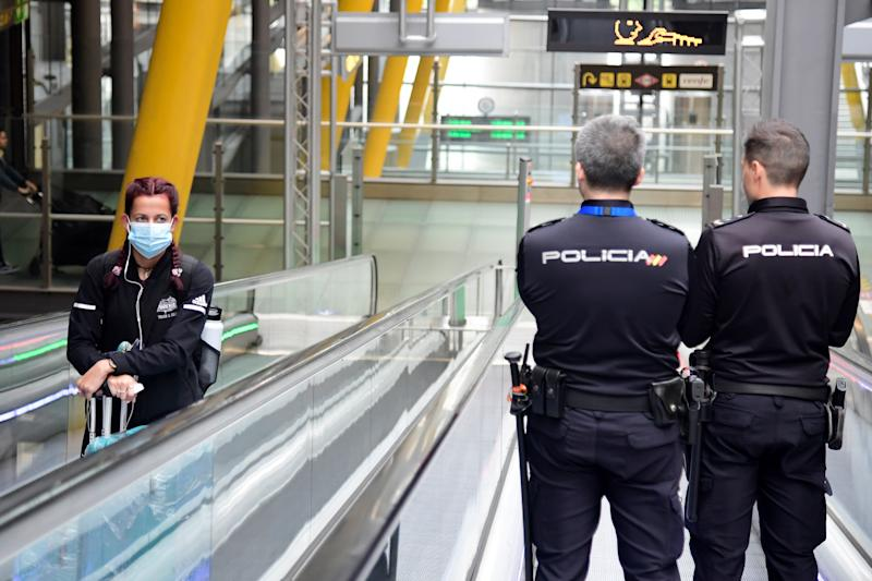A passenger wearing a face mask as a protective measure looks at two police officers as they use a travelator at the Madrid-Barajas Adolfo Suarez Airport in Barajas on March 20, 2020. - The coronavirus toll in Spain rose to 1,002 today following the deaths of 235 people in the past 24 hours, the health ministry said. The number of cases also soared to 19,980, after another 2,833 infections were confirmed over the same period, the ministry's emergencies coordinator said. (Photo by JAVIER SORIANO / AFP) (Photo by JAVIER SORIANO/AFP via Getty Images)