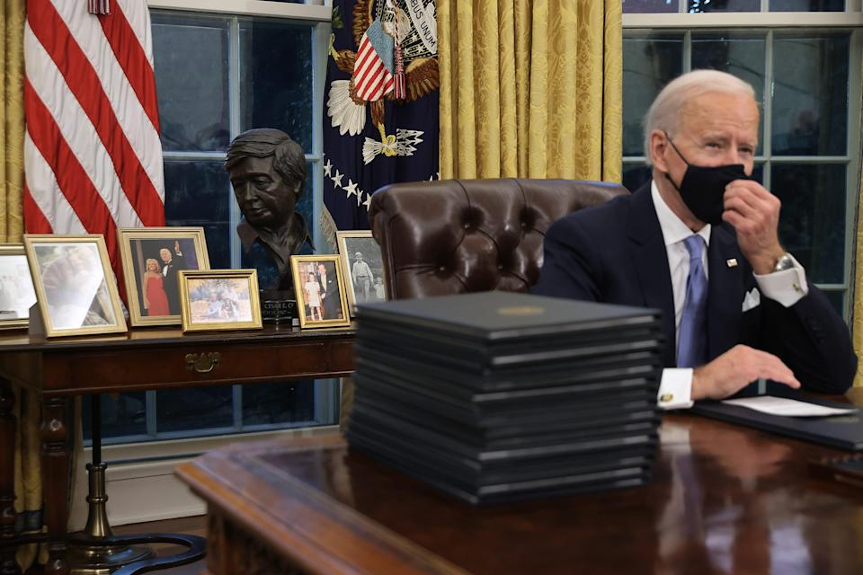Joe Biden signs a series of executive orders in the Oval Office hours after his inauguration on Jan. 20 as the 46th president of the United States.