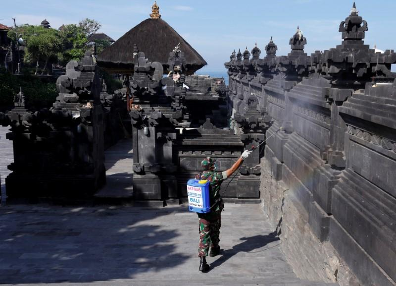 An Indonesian soldier sprays disinfectant to prevent the spread of coronavirus disease (COVID-19) at Tanah Lot temple in Tabanan, Bali