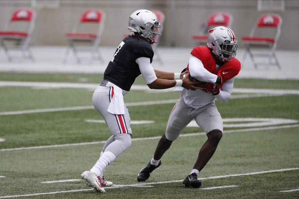 File-This Oct. 3, 2020, file photo shows Ohio State quarterback C.J. Stroud, left, handing the ball to running back Trey Sermon during their NCAA college football practice in Columbus, Ohio. The overarching question this spring is who will be starting at quarterback when the Buckeyes open the season on Sept. 2 at Minnesota. The early departure of Justin Fields for the NFL left two untested backups pro-style quarterbacks Stroud and Jack Miller III, two of the top prep signal-callers in the country that Ohio State snagged in the 2020 recruiting class. (AP Photo/Jay LaPrete, File)