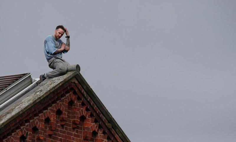 Prisoner Stuart Horner sits on the roof of Manchester's Strangeways prison , 15 September 2015.