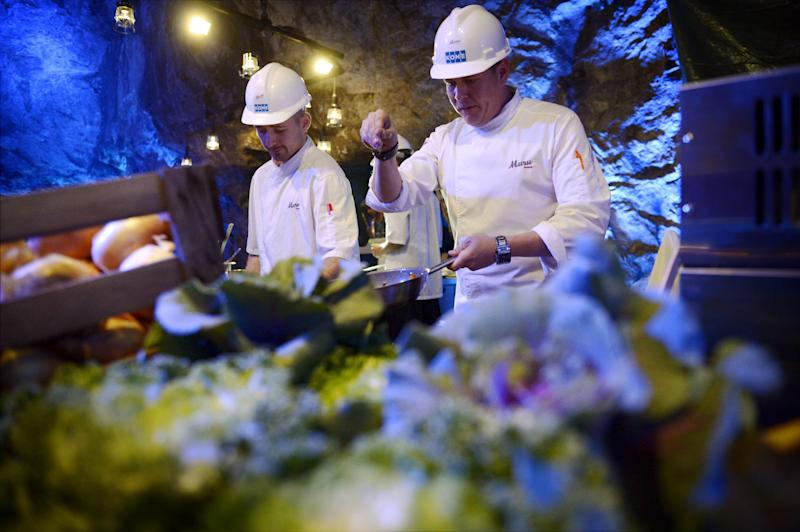 """Chef Niklas Ekblom, left, and restaurateur Timo Linnamaki preparing food at Muru Pop Down -restaurant at Tytyri mine in Lohja, Finland, Monday Sept. 10 2012. The award-winning chef is opening a new restaurant in Finland that turns the idea of """"pop-up"""" eateries upside-down: it's located 80 meters (260 feet) underground. Discerning food lovers are being served salted salmon, veal tenderloin snails cooked in Pernod, and apple crumble in the """"pop-down"""" restaurant in a limestone mine in the small, southern town of Lohja, 60 kilometers (40 miles) west of Helsinki. A four-course evening meal costs 128 euro ($160), including drinks and transportation down to the mine and back up. (AP Photo/Lehtikuva, Antti Aimo-Koivisto) FINLAND OUT"""