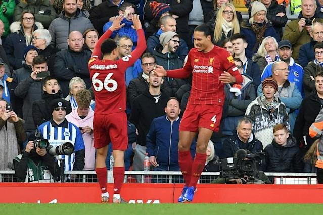 Double Dutch: Virgil van Dijk (right) scored both Liverpool's goals in a 2-1 win over Brighton (AFP Photo/Paul ELLIS)