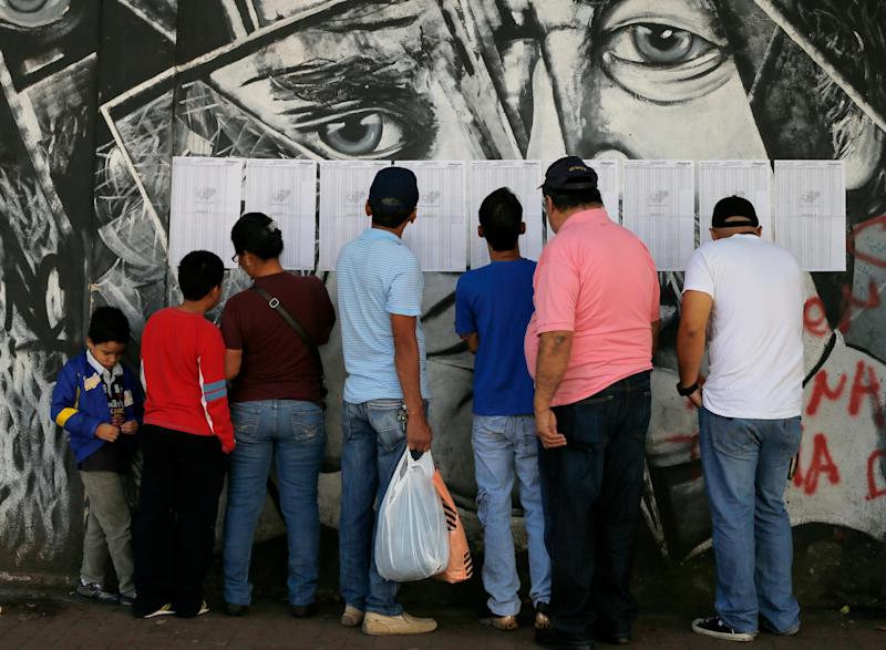 People look for their voting station on a list pasted on a wall outside of a public school in Caracas, Venezuela, Sunday, Dec. 8, 2013. Venezuelans head to the polls to elect mayors and city councilors at a moment when the country's economic troubles have deepened, with inflation touching a two-decade high of 54 percent, and shortages of everything from toilet paper to milk spreading while the black market value of the currency plunges. (AP Photo/Fernando Llano)