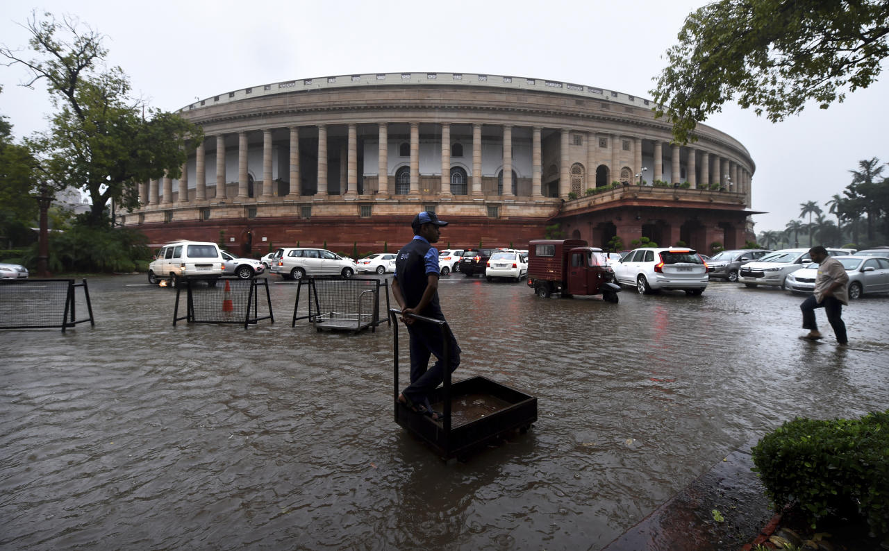 A worker stands on his handcart in a water logged area as lawmakers arrive amidst heavy downpour at the Parliament House in New Delhi, India, Tuesday, Aug. 6, 2019. India's lower house of Parliament was set to ratify a bill that would downgrade the governance of India-administered, Muslim-majority Kashmir. (AP Photo/Manish Swarup)