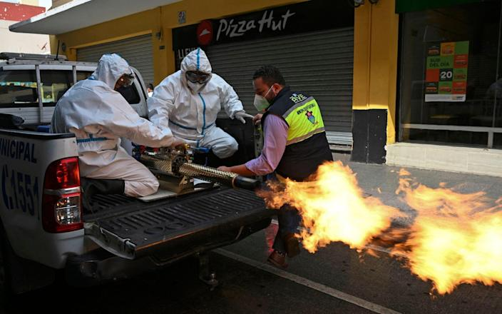Municipal workers wearing protective gear disinfect the streets after a spike in the number of positive coronavirus cases in Guatemala City - Johan ORDONEZ/AFP