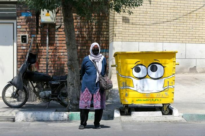 An Iranian woman stands next to a street bin, painted with a mask as part of a campaign to spread awareness about the coronavirus pandemic, in Tehran on July 18, 2020 (AFP Photo/ATTA KENARE)