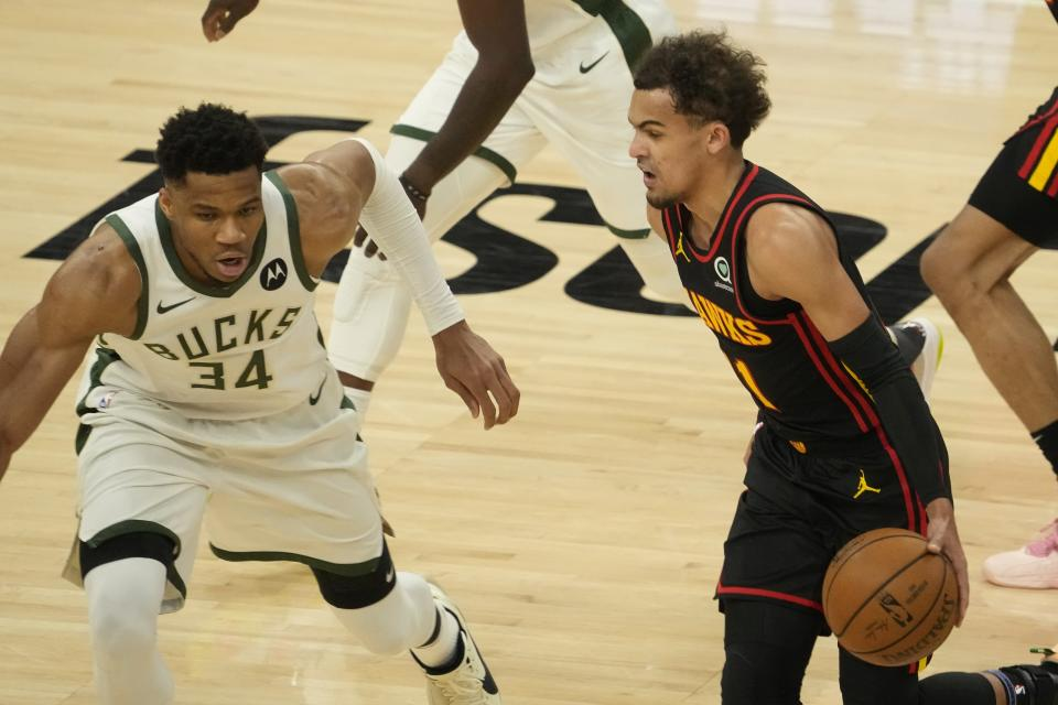 Atlanta Hawks' Trae Young tries to drive on Milwaukee Bucks' Giannis Antetokounmpo during the first half of Game 2 of the NBA Eastern Conference basketball finals game Friday, June 25, 2021, in Milwaukee. (AP Photo/Morry Gash)