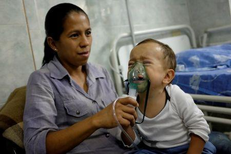 Dianis Salazar, carries her son Diego while he receives a breathing treatment in the pediatric emergency of the Universitary Hospital in Merida, Venezuela June 17, 2016. REUTERS/Marco Bello