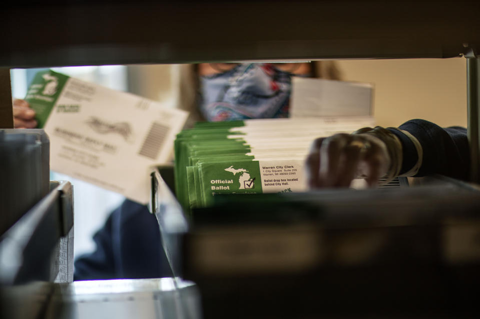 Election worker Mary Pluszczynsky files returned absentee ballots ahead of Tuesday's general election at the city clerk office in Warren, Mich., Wednesday, Oct. 28, 2020. (AP Photo/David Goldman)