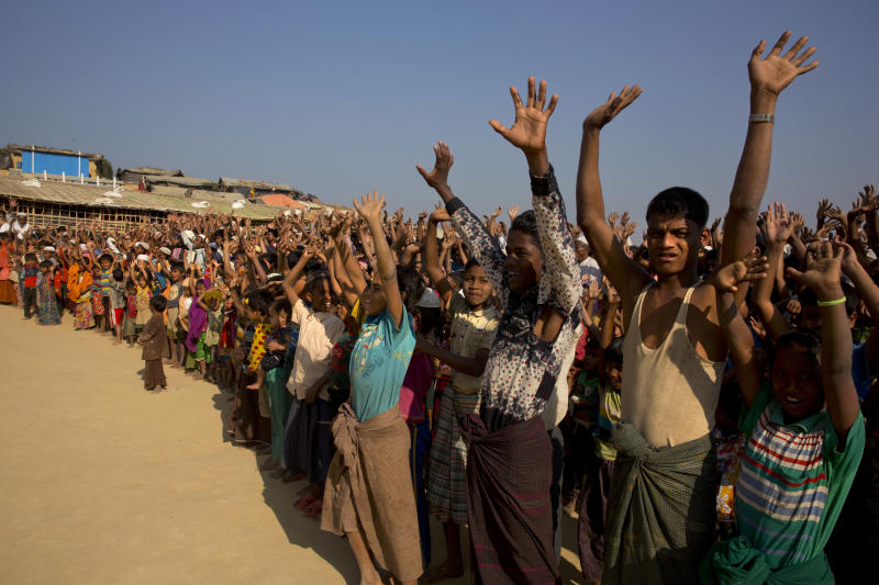 FILE - In this Jan. 22, 2018, file photo, Rohingya children and refugees raise their hands and shout that they won't go back to Myanmar during a demonstration at Kutupalong near Cox's Bazar, Bangladesh. Officials from the U.N. refugee agency and Bangladesh's government say few Muslim Rohingya refugees have responded to plans for their repatriation to Myanmar, and all who did say they don't want to go back. (AP Photo/Manish Swarup, File)