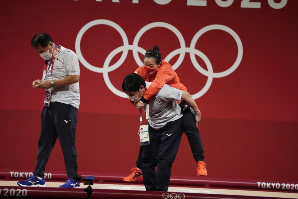 Mikiko Andoh of Japan cis carried by her coach Naoyuki Kobatake after winning the bronze medal in the women's 59kg weightlifting event, at the 2020 Summer Olympics, Tuesday, July 27, 2021, in Tokyo, Japan. She won gold medal and sets a new Olympic record. (AP Photo/Luca Bruno)