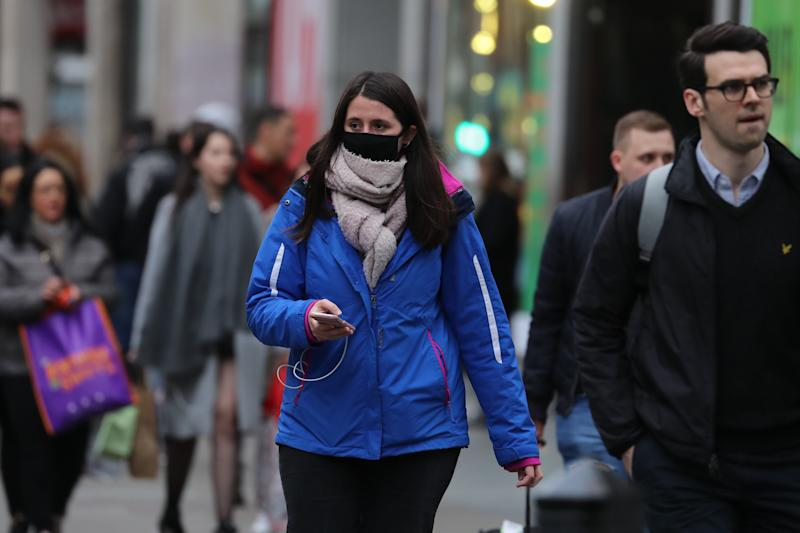 A woman wearing a face mask mask in Oxford Street in London, as Health Secretary Matt Hancock has said ministers are yet to make a decision on whether to ban gatherings of over 500 people in the rest of the UK, after Scotland said it would bring in restrictions from Monday.