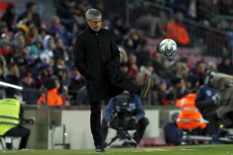 Barcelona's head coach Quique Setien kicks the ball back to the pitch during a Spanish La Liga soccer match between Barcelona and Granada at Camp Nou stadium in Barcelona, Spain, Sunday, Jan. 19, 2020. (AP Photo/Joan Monfort)