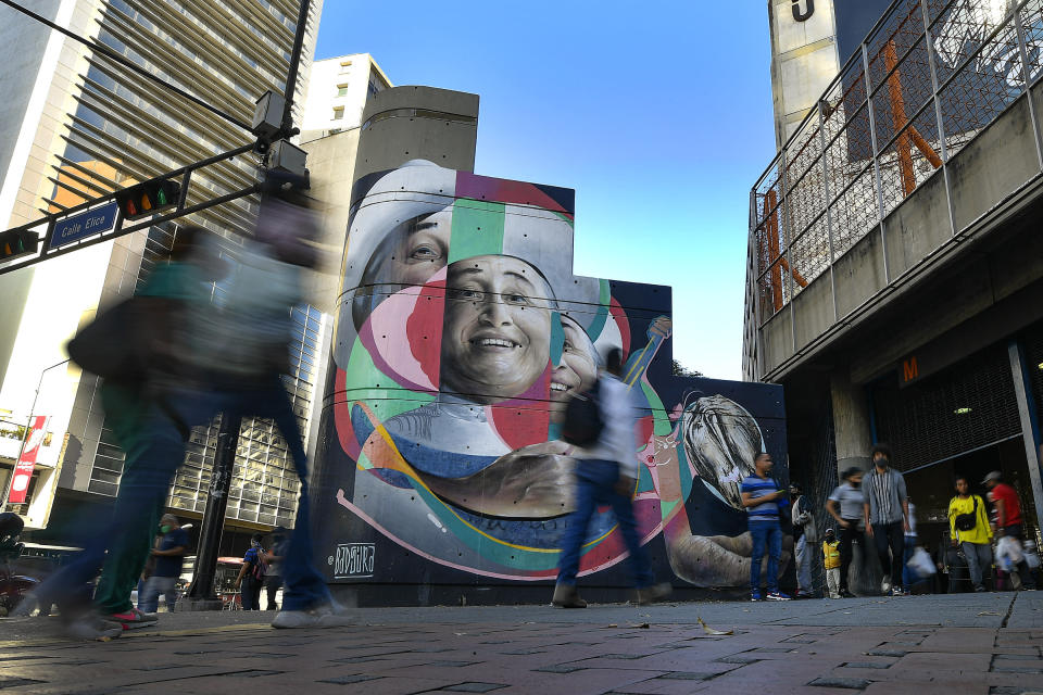 "Pedestrians walk past an art mural featuring singer and actor Simon Diaz painted by Wolfgang Salazar in the Chacao neighborhood of Caracas, Venezuela, Monday, Jan. 11, 2021. Salazar, who uses the artistic name of Badsura, a play on the English word ""bad"" and the Spanish word ""basura,"" for ""garbage,"" has gained increasing fame for his spray-painted murals of Venezuelans — heroes and everyday folk alike — at a time when the pandemic and economic hardship weigh upon his fellow citizens. (AP Photo/Matias Delacroix)"