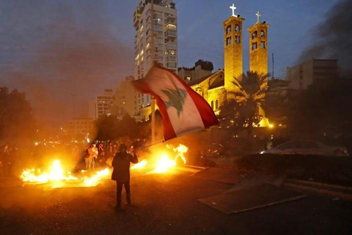 A Lebanese protester waves the national flag by a burning barricade during demonstrations in Beirut earlier this month (AFP Photo/JOSEPH EID)