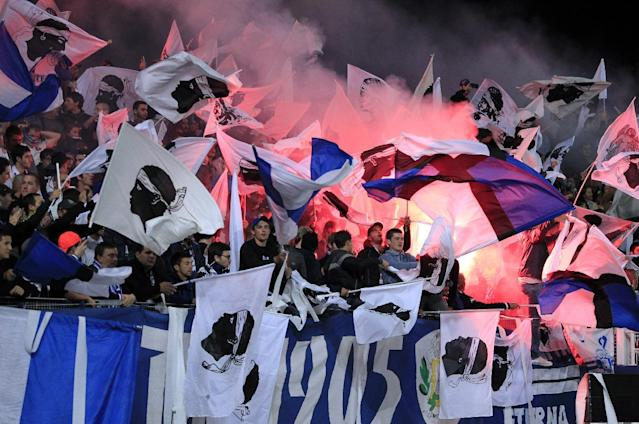 Bastia's supporters cheer for their team with Corsican flags and flares during the French L1 football match between Bastia and Monaco in Bastia on October 25, 2014 (AFP Photo/Pascal Pochard Casabianca)