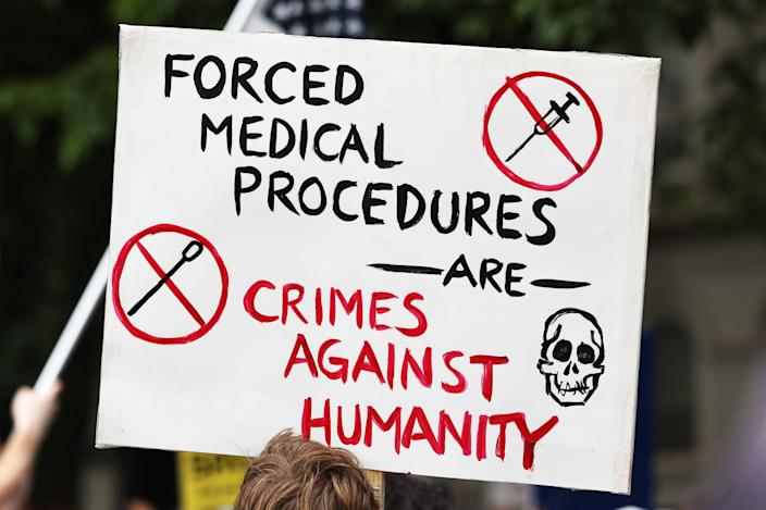 A person holds up a protest sign as people gather to protest vaccine mandates in New York City.