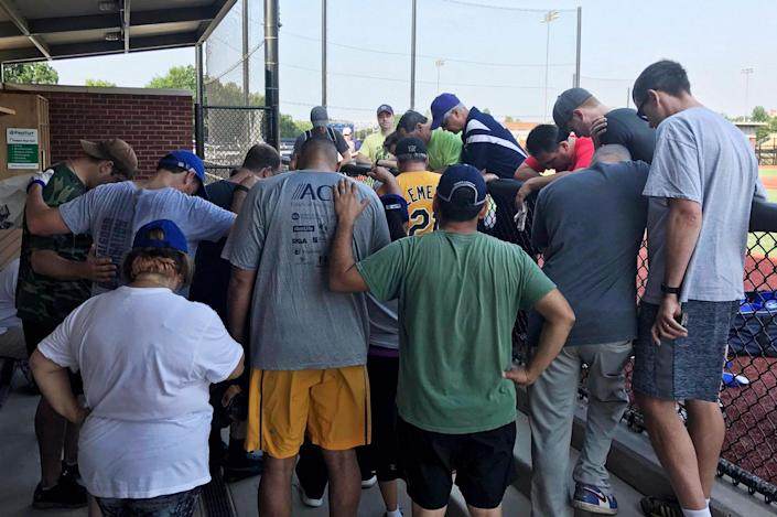 <p>House Democrats at a baseball field in Washington pray for their colleagues after hearing that a gunman fired on Republican lawmakers at a baseball practice in Alexandria, Va., Wednesday, June 14, 2017. A rifle-wielding attacker wounded House GOP Whip Steve Scalise of Louisiana and several others as congressmen and aides dove for cover. (Rep. Ruben J. Kihuen via AP) </p>