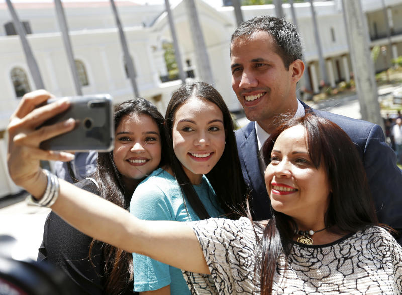 "Venezuelan opposition leader Juan Guaido, who has declared himself interim president, poses for selfie photo with supporters after a meeting with ""Frente Amplio,"" a coalition of opposition parties, and other civic groups in Caracas, Venezuela, Monday, March 18, 2019. After Guaido declared himself interim president in late Feb., Venezuelan President Nicolas Maduro has remained in power despite heavy pressure from the United States and other countries arrayed against him, managing to retain the loyalty of most of his military leaders. (AP Photo/Natacha Pisarenko)"