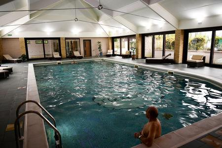 A resident relaxes in a swimming pool at The Thatchers Holiday Village in Modbury